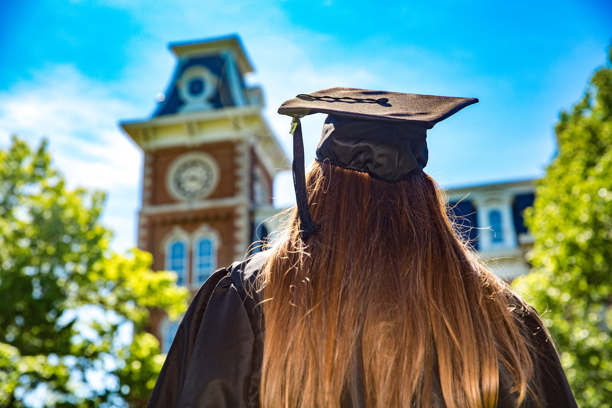 A student in a cap and gown faces Old Main