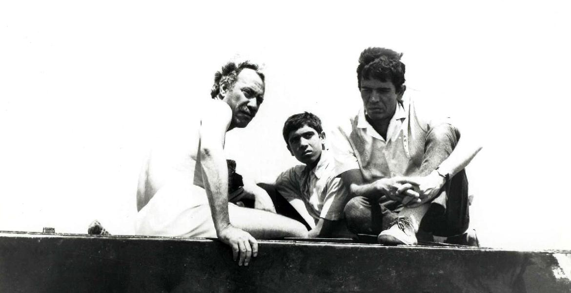 "Film still from ""The Dupes"" (Syria 1973, directed by Tewfik Saleh) depicting three adult men of various ages sitting atop the bed of a truck"