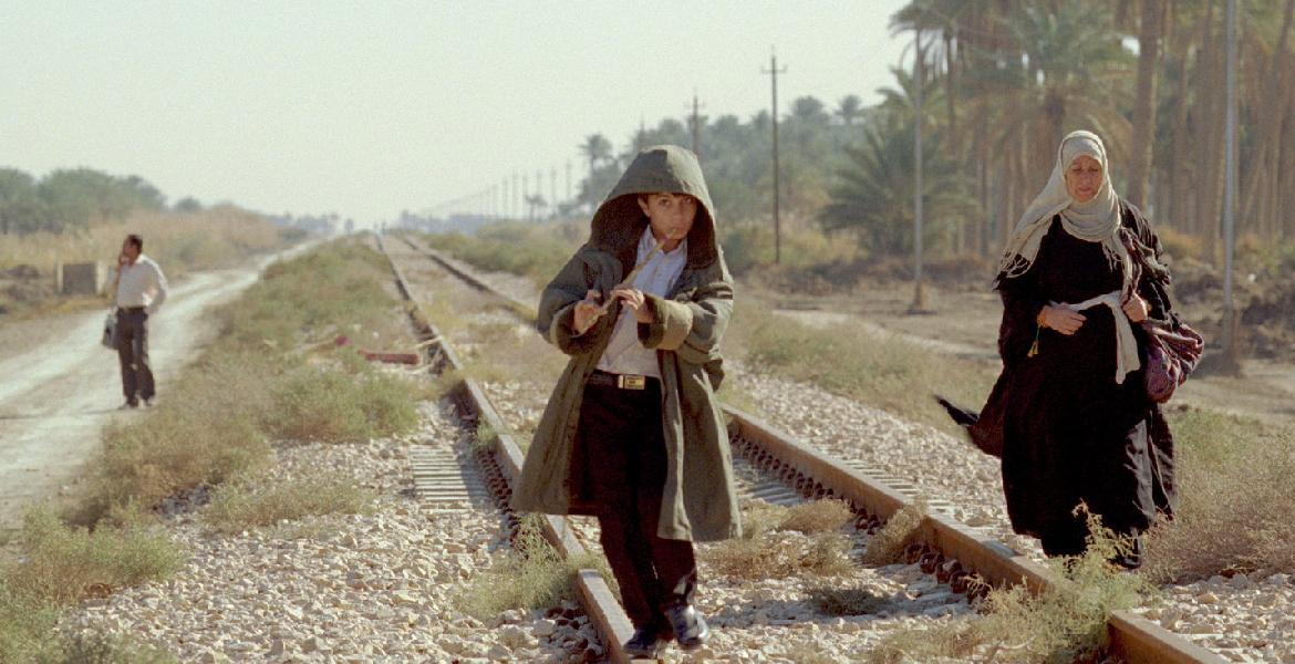 Film still from Son of Babylon (Iraq 2010, directed by Mohamed al-Daradji) depicting a young boy playing the flute walking on train tracks with his grandmother