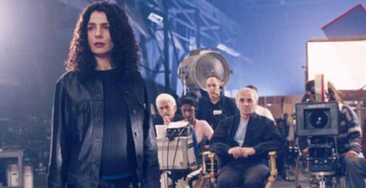 "Film still from ""Ararat"" (Canada 2020, directed by Atom Egoyan) depicting a woman with dark hair in the foreground of a film set with recording equipment, crew and director seated behind her"