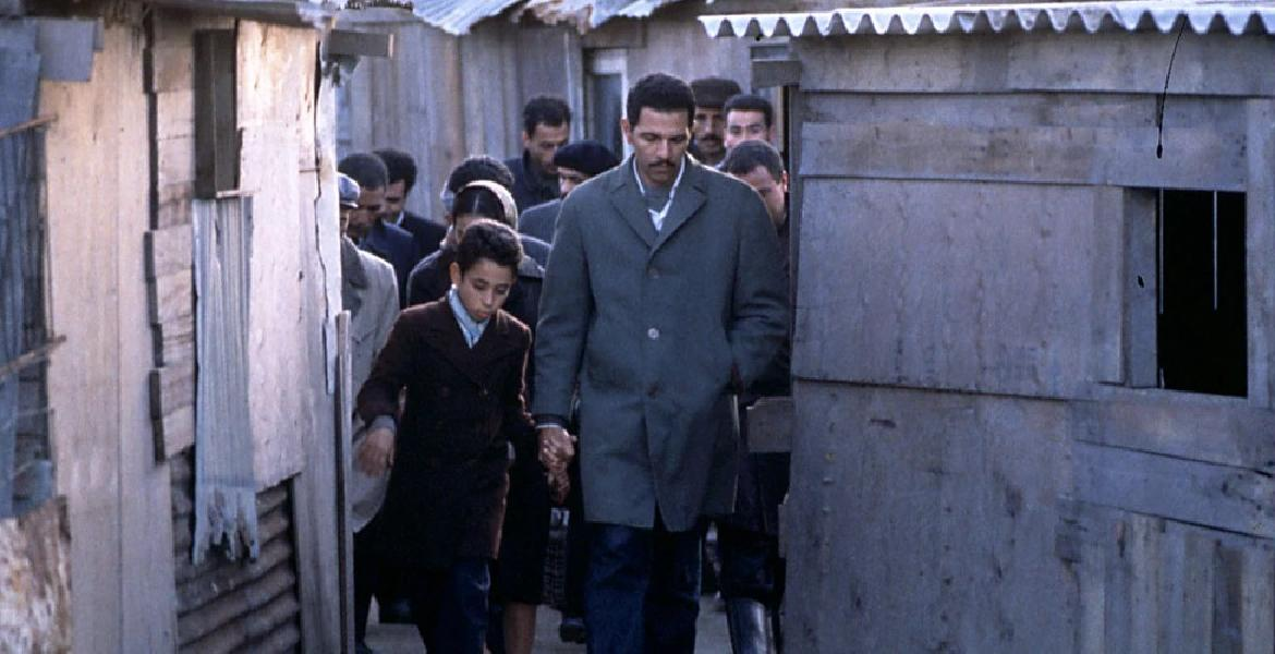 "Film still from ""Living in Paradise"" (Algeria/France 1998, directed by Bourlem Guerdjou) depicting a young boy walking hand in hand with his father through a narrow alleyway, followed by a crowd of other people"