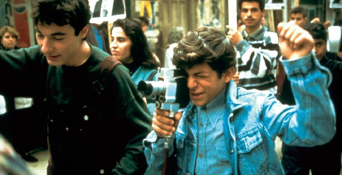 "Film still from ""West Beirut"" (Lebanon 1998, directed by Ziad Doueiri) depicting two young men, the primary in a blue jacket filming with a vintage video camera."