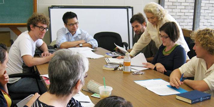 A group of students and a faculty member collaborating at a round table.